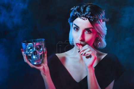 sexy vampire woman holding skull with blood and licking her fingers isolated on black
