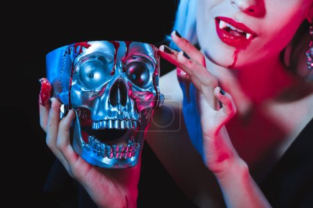 cropped view of vampire holding metal skull with blood isolated on black