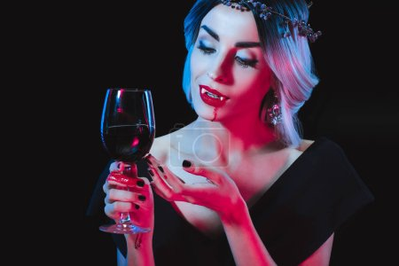 Photo for Sexy vampire woman holding wineglass with blood isolated on black - Royalty Free Image