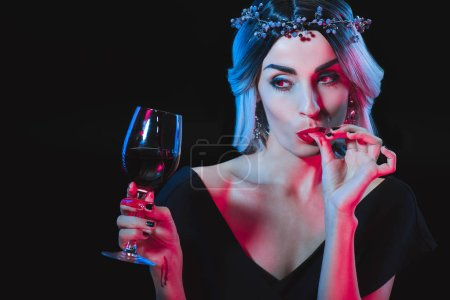 Photo for Vampire woman holding wineglass with blood and licking her fingers isolated on black - Royalty Free Image