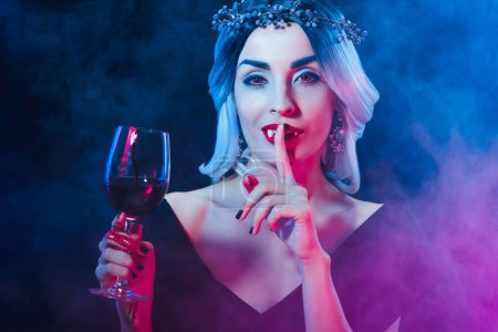 vampire holding wineglass with blood and showing silence symbol on darkness with smoke