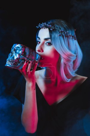 sexy vampire woman drinking blood from metal skull on dark background with smoke