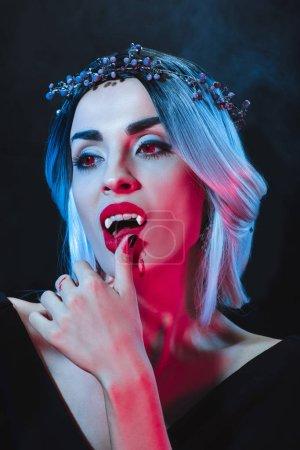 beautiful vampire woman touching her lips on dark background with smoke