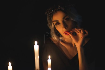 beautiful woman in vampire costume licking her fingers with candles on foreground isolated on black