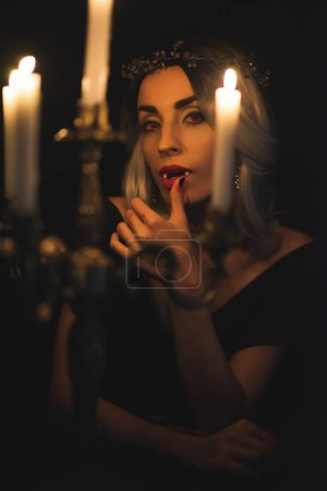 woman in vampire costume licking her fingers with candelabrum on foreground