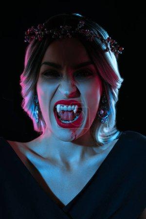 vampire woman showing vampire teeth isolated on black