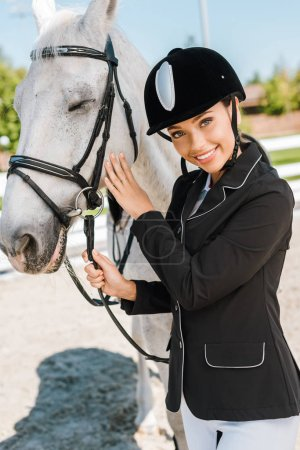 attractive female equestrian in riding helmet looking at camera near white horse at horse club