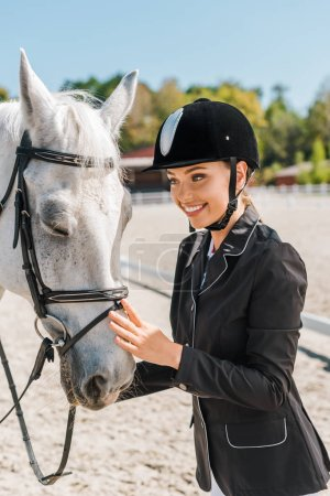 attractive smiling female equestrian standing near horse at horse club