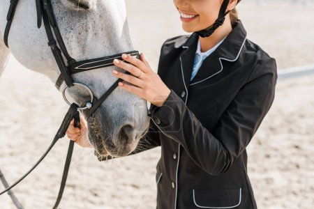 cropped image of smiling female equestrian palming horse at horse club