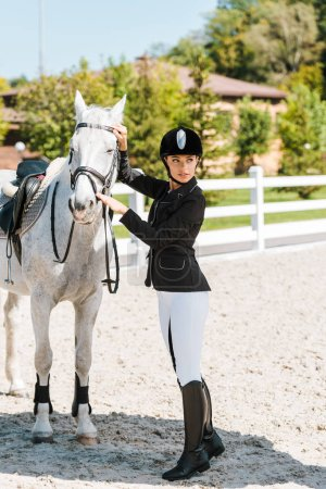 attractive female equestrian fixing horse halter and looking away at horse club