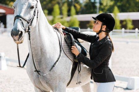 Photo pour Séduisante équestre féminin fixation selle de cheval à horse club - image libre de droit