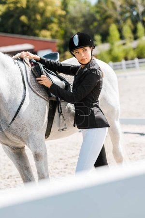 Photo pour Belle équestre féminin fixation selle de cheval à horse club - image libre de droit