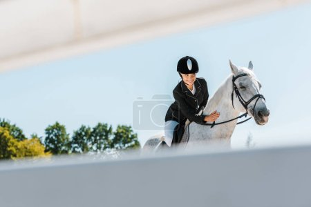 Photo for View through fence on attractive female equestrian riding and palming horse at horse club - Royalty Free Image