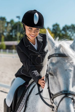 smiling attractive female equestrian in professional apparel riding horse at horse club