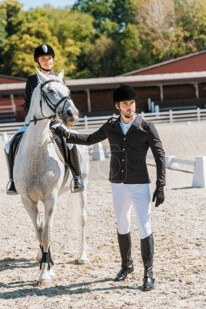 Foto de Guapos macho jinetes con halter del caballo, jockey femenino sentado a caballo en el club del caballo - Imagen libre de derechos