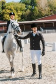 handsome male equestrians holding horse halter, female jockey sitting on horse at horse club
