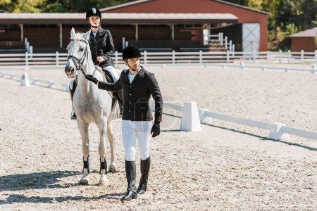 Foto de Jinetes guapos sosteniendo halter del caballo, jockey femenino sentado a caballo en el Rancho - Imagen libre de derechos