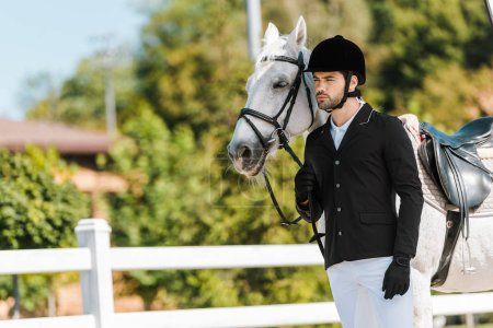 handsome male equestrian standing near horse at horse club
