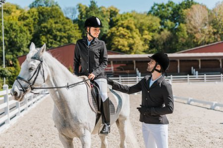 Photo for Female and male equestrians looking at each other at horse club - Royalty Free Image