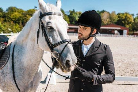 Photo pour Sérieux beau mâle équestre fixation cheval licol à horse club - image libre de droit