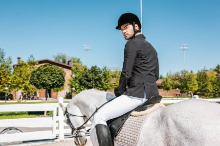 handsome male equestrian in professional apparel sitting on horseback at horse club