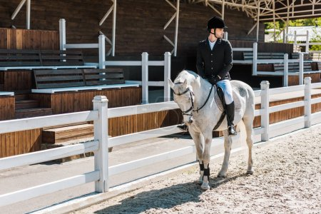 handsome male equestrian riding horse at horse club