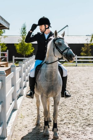 handsome male equestrian riding horse at horse club and touching riding helmet
