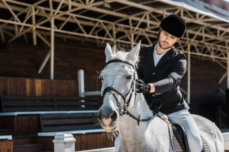 handsome male equestrian riding and palming horse at horse club