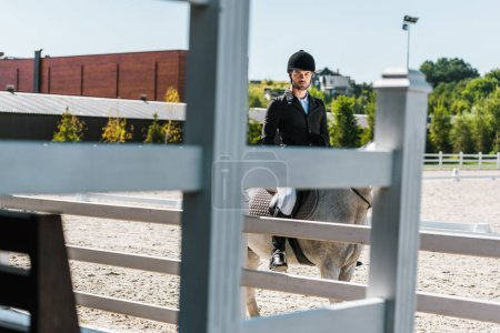 view through fence on handsome male equestrian riding horse at horse club and looking at camera