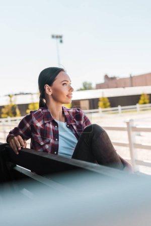 Foto de Vista lateral de vaquera atractiva en camisa a cuadros sentado sobre un banco en el estadio de Rancho y mirando lejos - Imagen libre de derechos