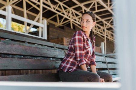 Foto de Hermosa vaquera en camisa a cuadros sentado sobre un banco en el estadio de Rancho y mirando lejos - Imagen libre de derechos