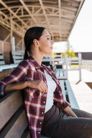 Photo pour Vue de côté de belle cowgirl en chemise à carreaux assis sur un banc au stade ranch et la recherche. - image libre de droit
