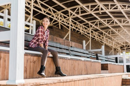 Photo for Smiling beautiful woman in casual clothes sitting on bench at ranch stadium - Royalty Free Image