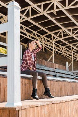 Foto de Vaquera atractiva en camisa a cuadros sentado sobre un banco en el estadio de Rancho y mirando algo - Imagen libre de derechos