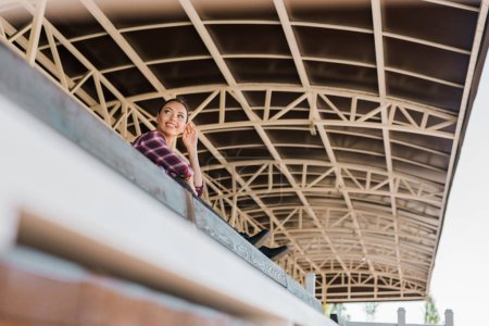 Foto de Vista de ángulo bajo de vaquera atractiva en camisa a cuadros sentado sobre un banco en el estadio de Rancho - Imagen libre de derechos