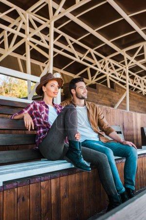 Photo pour Cowboy et cowgirl assis sur un banc au stade ranch et la recherche. - image libre de droit