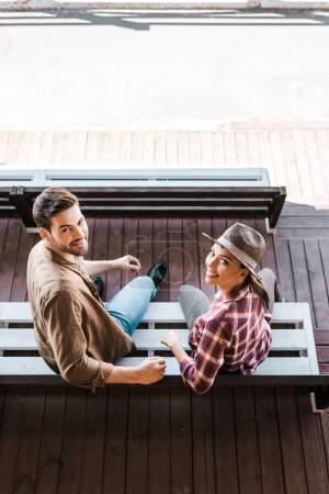 high angle view of smiling cowboy and cowgirl in casual clothes sitting on bench at ranch stadium