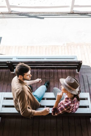 Photo for High angle view of cowboy and cowgirl sitting on bench at ranch stadium and looking at each other - Royalty Free Image