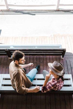 Foto de Vista de ángulo alto de vaquero y vaquera sentado sobre un banco en el estadio de Rancho y mirando el uno al otro - Imagen libre de derechos