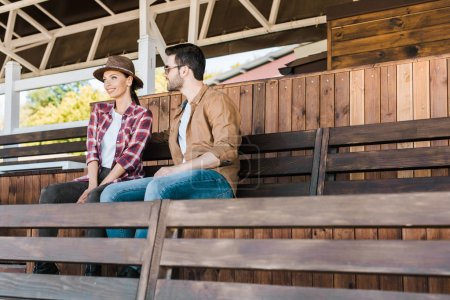 cheerful cowboy and cowgirl in casual clothes sitting on bench at ranch stadium
