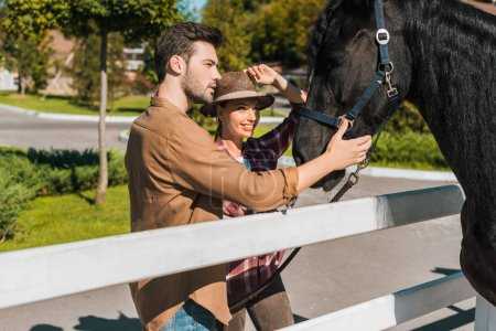 female and male equestrians palming black horse at ranch
