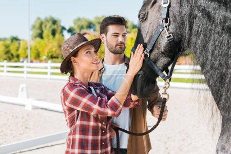 Photo pour Cowboy et cowgirl en vêtements décontractés palming cheval noir au ranch - image libre de droit