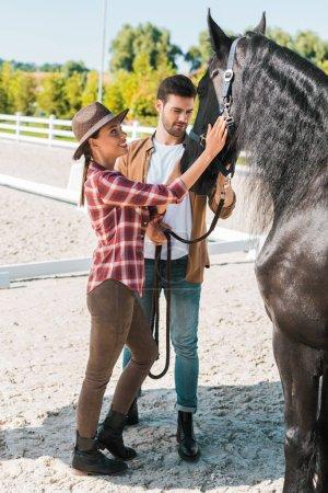 Photo pour Mâles et femelles jockeys palming cheval noir au ranch - image libre de droit