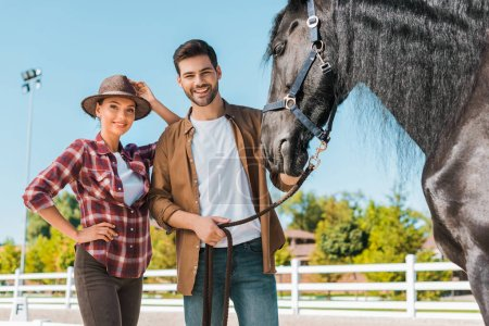 Photo for Smiling female and male equestrians standing near horse at ranch and looking at camera - Royalty Free Image