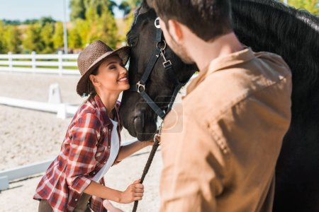 beautiful equestrian in hat hugging black horse at ranch