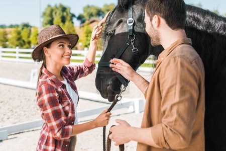 cheerful cowboy and cowgirl looking at each other near horse at ranch