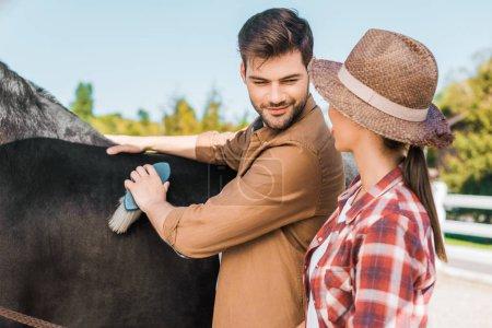 Photo pour Équitation aux jeux mâle beau cheval noir avec brosse au ranch de nettoyage et en regardant la femme au chapeau - image libre de droit