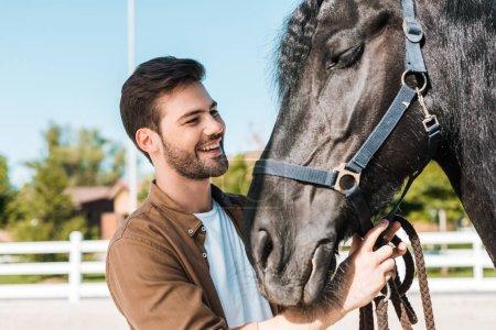 Photo pour Sourire beau cowboy fixation cheval licol à cheval club - image libre de droit