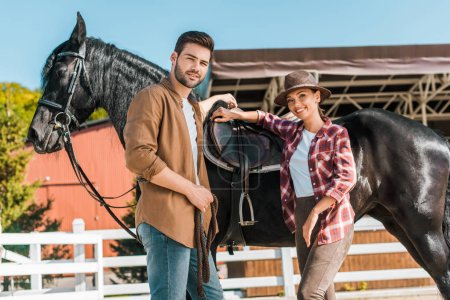 low angle view of cowboy and cowgirl standing near horse at ranch and looking at camera