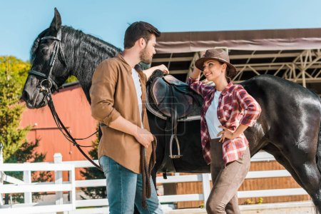 Photo for Low angle view of female and male equestrians standing near horse and talking at ranch - Royalty Free Image